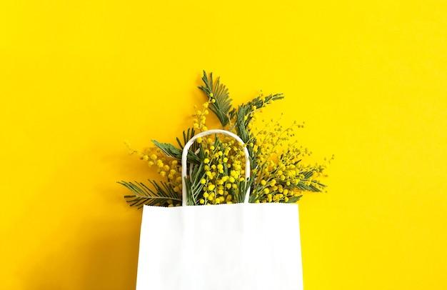 Ein strauß mimosen in einer weißen mock-up-geschenktüte. frühlingseinkäufe, geschenke und aktionen für den internationalen frauentag. gelber hintergrund, copyspace.