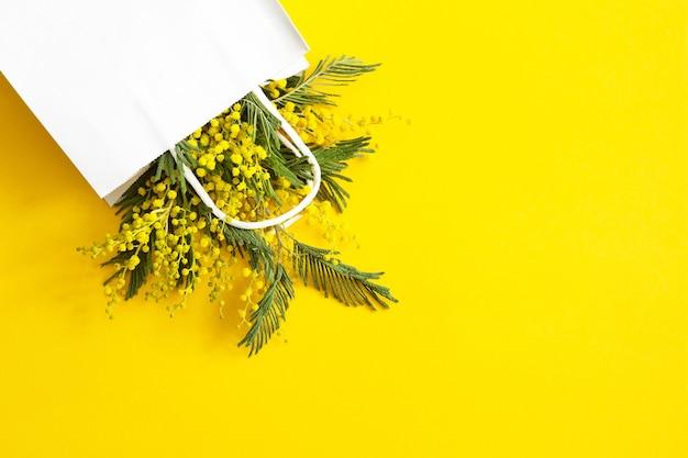 Ein strauß mimosen in einer weißen mock-up-geschenktüte. frühlingseinkäufe