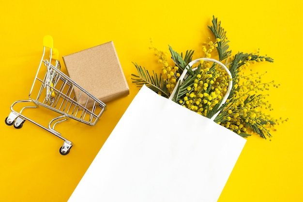 Ein strauß mimosen in einer weißen papiertüte, einer geschenkbox und einem einkaufswagen.