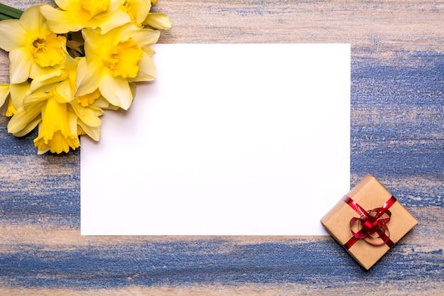 Ein strauß narzissen, ein geschenk mit einem roten band und einem blatt weißem papier auf einem hölzernen hintergrund.