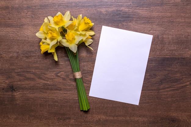 Ein strauß narzissen und ein blatt weißes papier auf einem hölzernen hintergrund