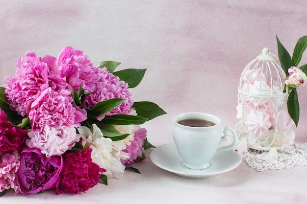 Ein strauß pfingstrosen, eine tasse tee und ein dekorativer käfig mit baiser