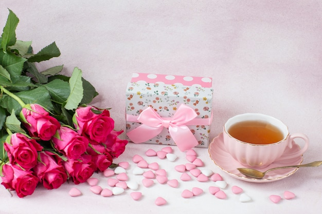 Ein strauß rosa rosen, ein geschenk in einer schachtel, herzförmige süßigkeiten und tee in einer tasse