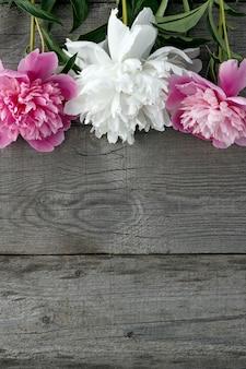 Ein strauß rosa und weiß blühender pfingstrosen auf der oberfläche der alten bretter mit textur