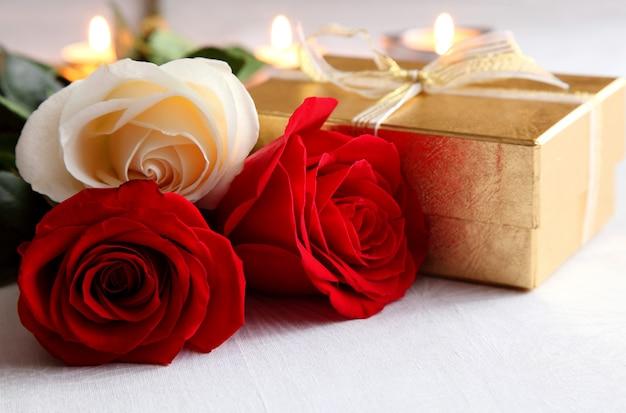 Ein strauß rosen und ein geschenk auf dem hintergrund der brennenden kerzen. valentinstag.