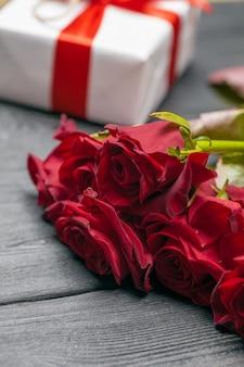Ein strauß roter rosen, geschenk und herzen auf dem tisch. konzept frauentag oder st. valentine. kopieren sie platz