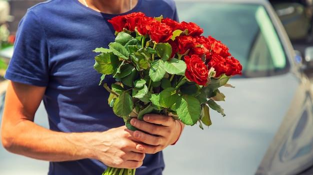 Ein strauß roter rosen in den händen eines mannes.