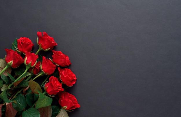 Ein strauß roter rosen mit auf einem schwarzen hintergrund