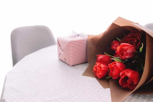 Ein strauß roter tulpen auf dem tisch und rosa geschenkbox. konzept des valentinstags