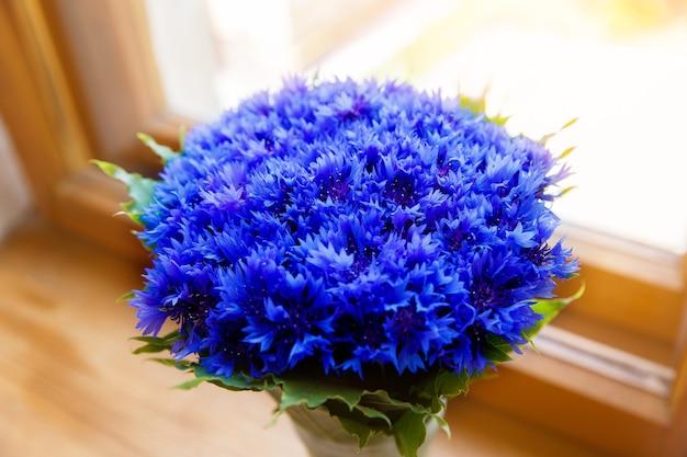 Ein strauß schöner frühlingsblumen blaue kornblume cyanus auf dem fenster. blaues blumenmuster. makrofoto.
