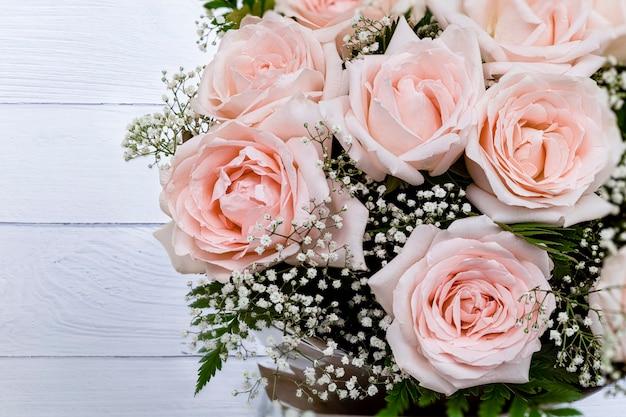 Ein strauß schöner rosa rosen auf weißem holzhintergrund.