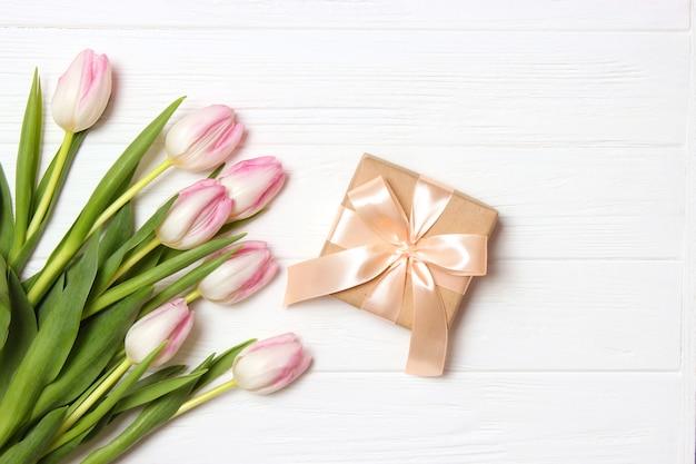 Ein strauß schöner tulpen und ein geschenk auf einer draufsicht des hölzernen hintergrundes