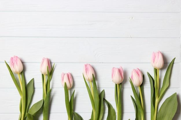Ein strauß tulpen auf einem hölzernen hintergrund draufsicht frühlingshintergrund