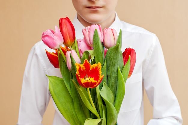 Ein strauß tulpen in den händen eines jungen in einem weißen hemd