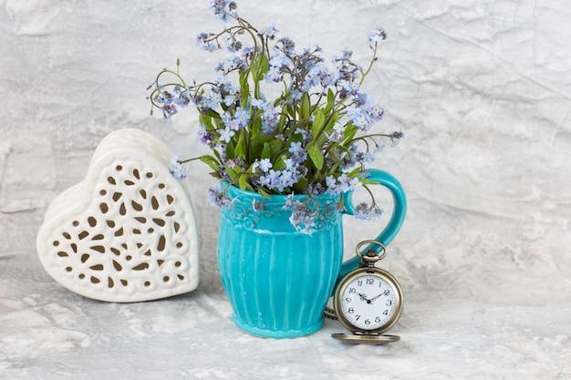 Ein strauß vergissmeinnicht, ein durchbrochenes keramikherz und eine taschenuhr
