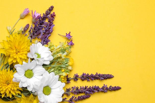 Ein strauß verschiedener wildblumen auf gelbem grund mit platz für die inschrift.