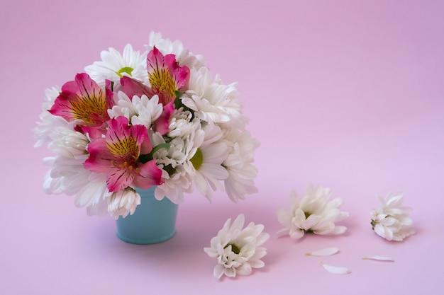 Ein strauß weißer chrysanthemen mit rosa alstroemeria in einem blauen eimer an einer rosa wand