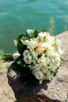 Ein strauß weißer rosen am steinernen ufer des flusses