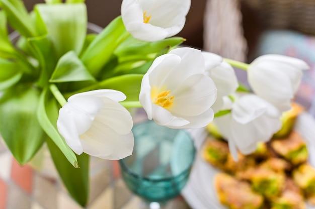 Ein strauß weißer tulpen auf einem tisch diente zum mittagessen