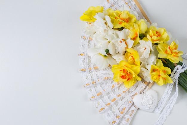 Ein strauß weißer und gelber narzissen, ein spitzenfächer und ein herz
