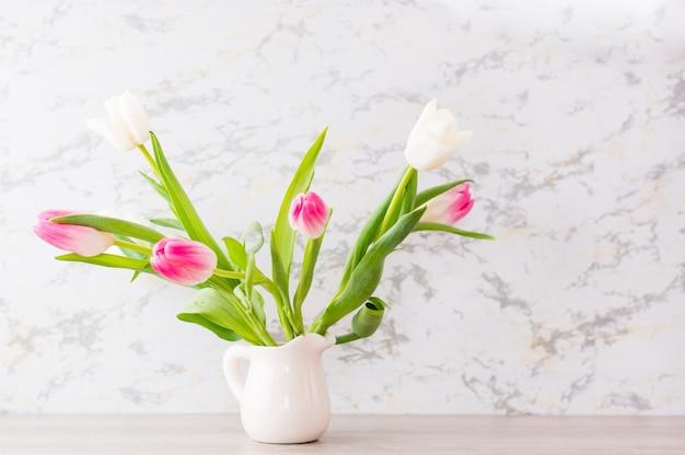 Ein strauß weißer und rosa tulpen mit grünen blättern steht in einem krug auf dem tisch. selektiver fokus. zarte postkarte