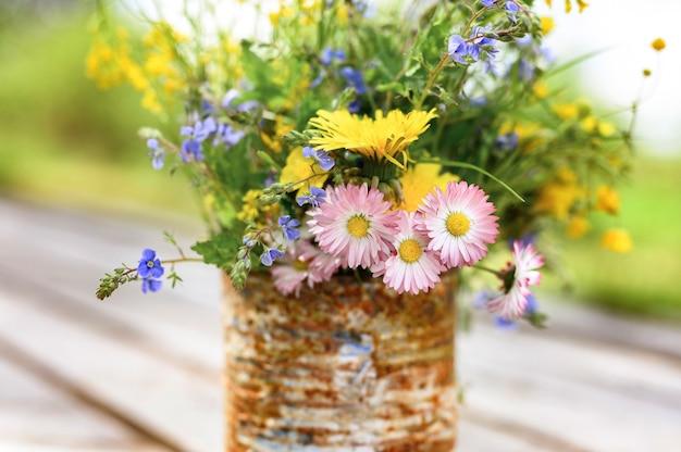 Ein strauß wildblumen in einem rostigen rustikalen glas gegen holzbretter.