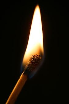 Ein streichholz in flamme über schwarz