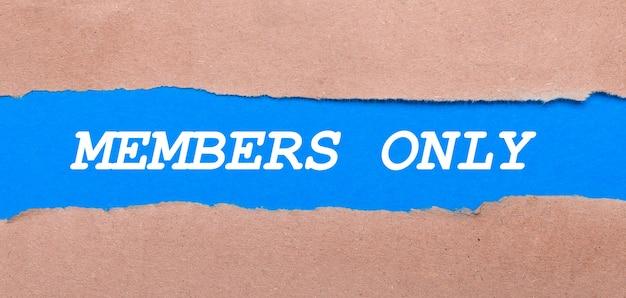 Ein streifen blaues papier mit der aufschrift nur mitglieder zwischen dem braunen papier. sicht von oben