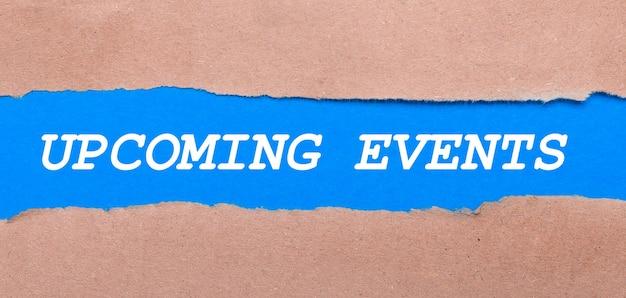 Ein streifen blaues papier mit der aufschrift upcoming events zwischen dem braunen papier. sicht von oben