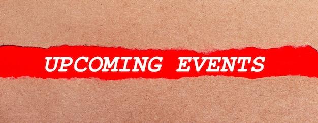 Ein streifen rotes papier unter dem zerrissenen braunen papier. weiße schrift auf rotem papier bevorstehende veranstaltungen. sicht von oben