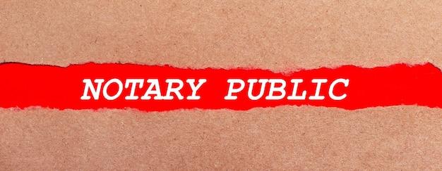 Ein streifen rotes papier unter dem zerrissenen braunen papier. weiße schrift auf rotem papier notary public. sicht von oben