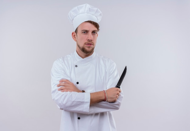 Ein strenger junger bärtiger kochmann in der weißen uniform, die ein messer mit gefalteten händen hält, während er auf eine weiße wand schaut