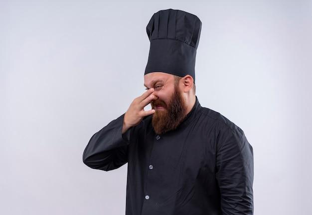 Ein stressiger bärtiger kochmann in der schwarzen uniform, die weint und negativität auf einer weißen wand zeigt