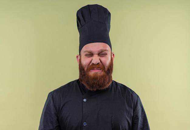 Ein stressiger bärtiger kochmann in der schwarzen uniform weint, während er auf eine grüne wand schaut