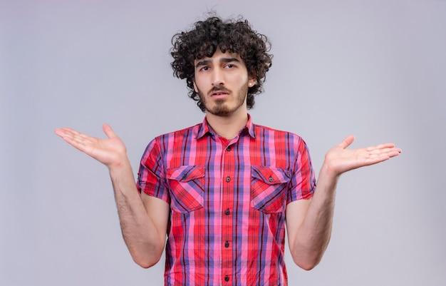 Ein stressiger gutaussehender mann mit lockigem haar in kariertem hemd, mit offenen armen