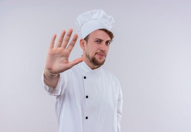 Ein stressiger junger bärtiger kochmann, der weiße kochuniform und hut trägt, die stoppgeste mit hand zeigen, während auf einer weißen wand schauen