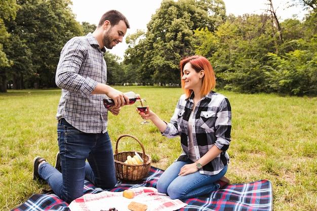 Ein strömender wein der jungen frau im glasgriff durch ihre frau am picknick im park
