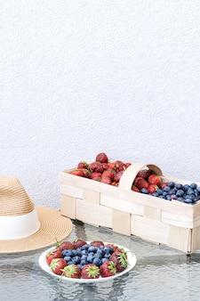Ein strohhut, frische erdbeeren und blaubeeren liegen in einem teller und korb auf einem glastisch