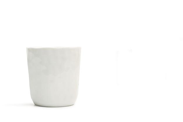 Ein strukturiertes weißes keramikglas auf einem weißen hintergrund