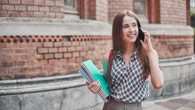 Ein student mit bunten notizbüchern und einer tasche läuft in der nähe des campus und telefoniert