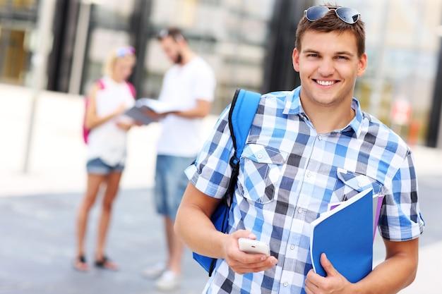 Ein student mit smartphone auf dem campus