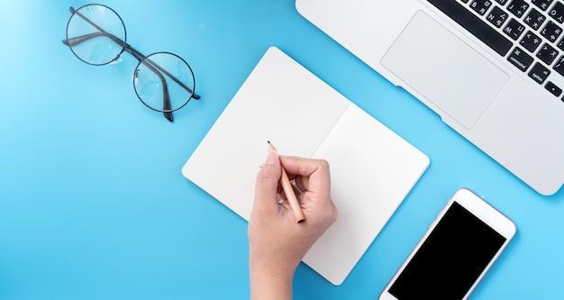 Ein student schreibt auf offenem weißbuch oder buchhaltung isoliert auf einem minimal sauberen blauen arbeitsplatz zu hause mit smartphone und zubehör, kopierraum, flachem liegen, draufsicht, modell