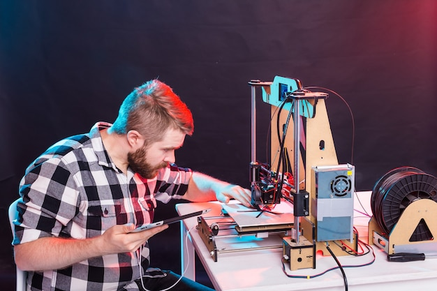 Ein studentenmann druckt prototyp auf 3d-drucker.