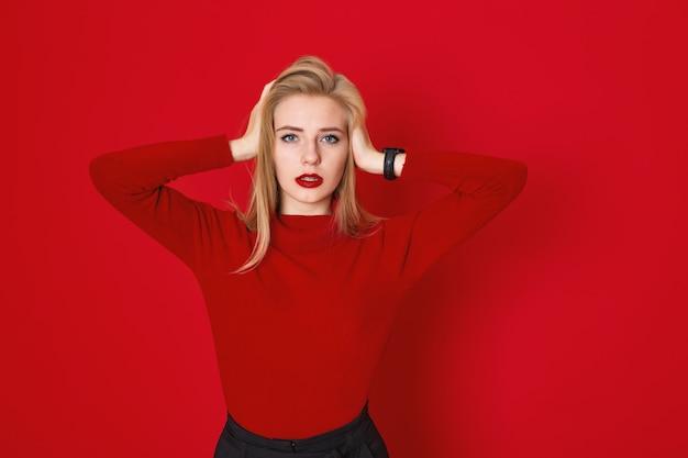 Ein studio, das von langhaarigem blone mädchen geschossen wird, trägt zufälliges rotes t-shirt. frau, die ihren kopf innen hält