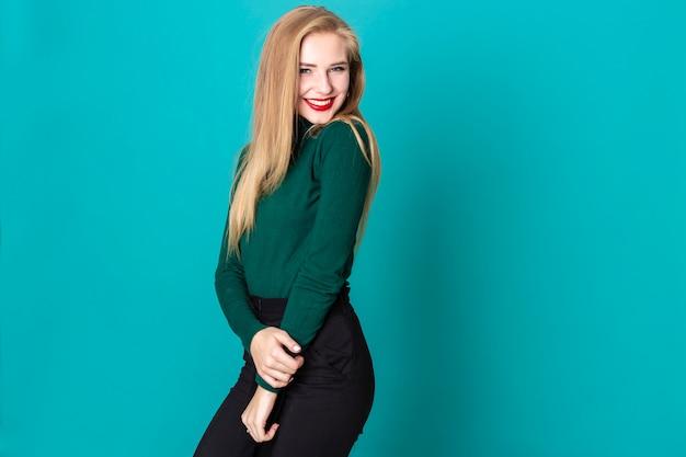 Ein studio schoss von der verlockenden blonden frau, die playfully die kamera betrachtet