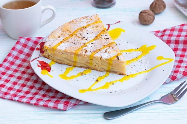 Ein stück apfelkuchen auf einem teller. dekorationen mit puderzucker, zimt und topping.