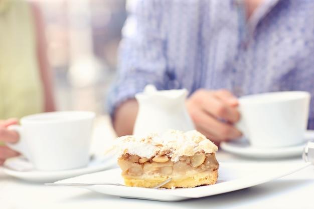 Ein stück apfelkuchen auf einem weißen teller in einem café serviert