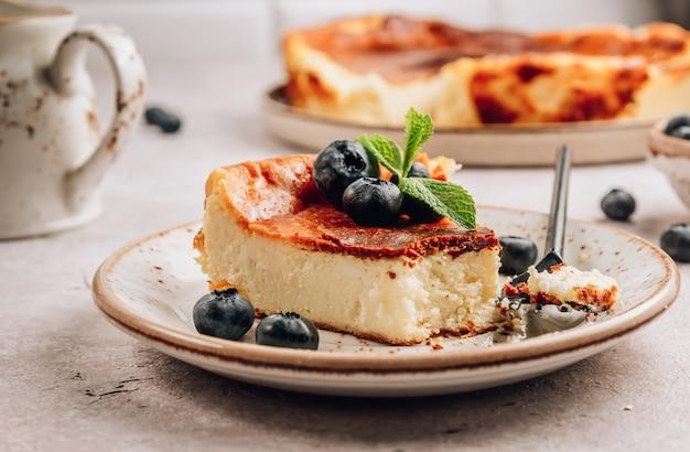 Ein stück baskischer gebrannter käsekuchen, der ganze kuchen ist im hintergrund. tarta de queso.
