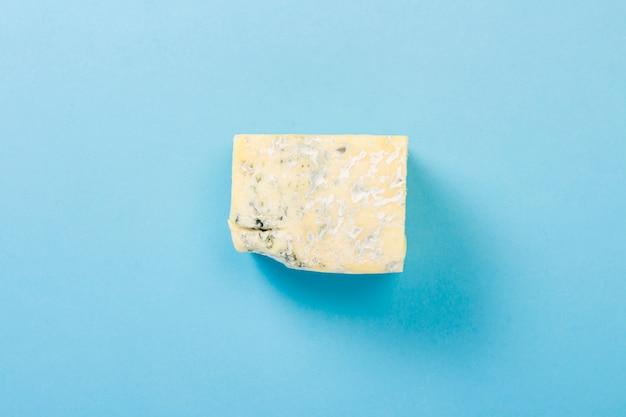 Ein stück blauschimmelkäse auf einer blauen oberfläche. minimalismus. flachgelegt, draufsicht.