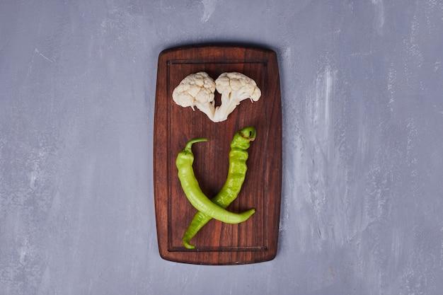 Ein stück blumenkohl mit grünen chilis.